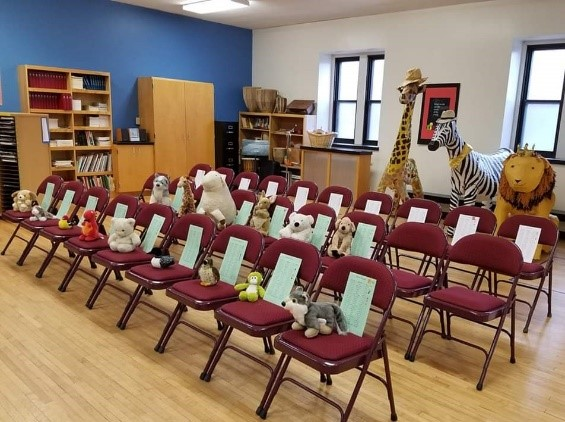 A choir room with no people in it. Stuffed animals sit on each chair.